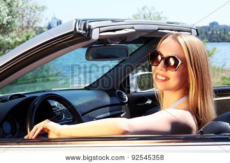 Pretty girl in cabriolet, outdoors