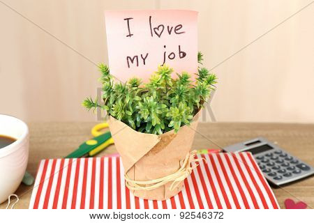 Inscription I love my job in flowerpot on workplace