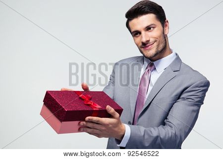 Businessman giving gift box to something over gray background
