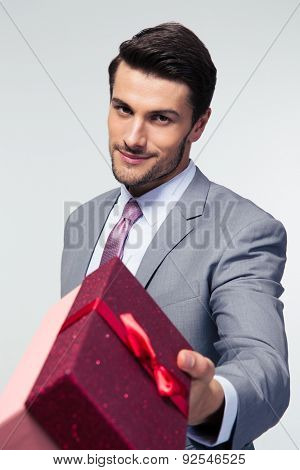 Happy businessman giving gift box on camera over gray background