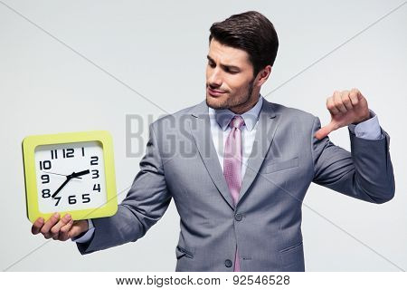 Businessman holding clock and showing thumb down over gray background