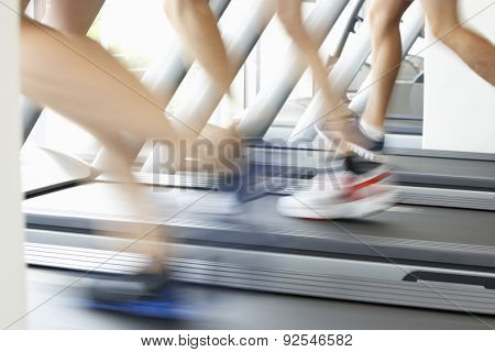 Close Up Of 3 Runners Feet On Running Machine In Gym