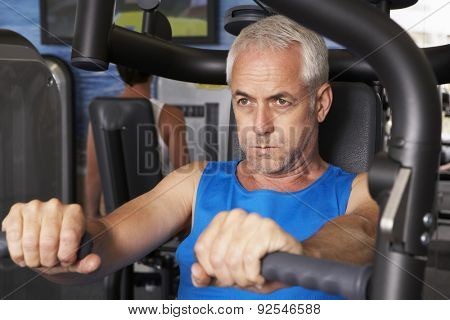 Middle Aged Man Using Weights Machine In Gym
