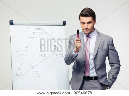 Businessman making presentation on flipchart over gray background. Looking at camera