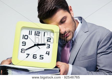 Portrait of a sleeping businessman holding folders and clock over gray background