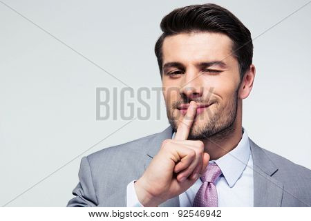 Businessman pointing finger over lips, asking for silence  over gray background. Looking at camera