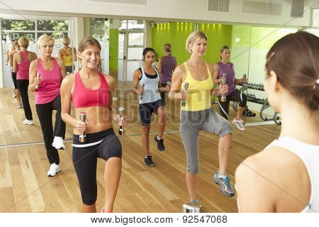 Women Taking Part In Gym Fitness Class Using Weights