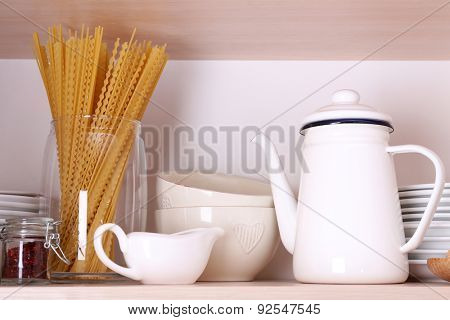 Kitchen utensils and tableware on wooden shelf