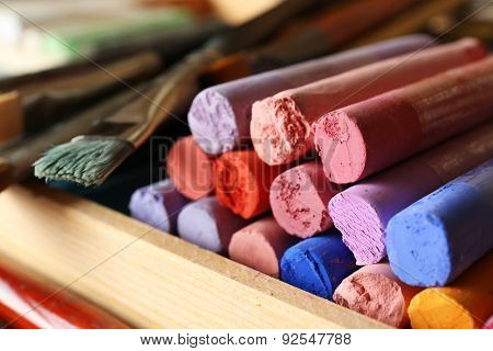Paintbrushes with colorful chalk pastels in box close up
