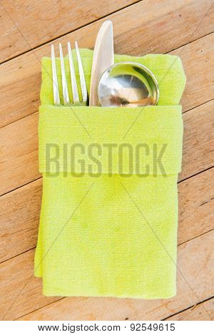 table setting, silverware and eating concept - close up of cutlery set wrapped to napkin on restaurant table