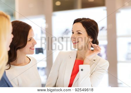 sale, consumerism, shopping and people concept - happy happy women choosing and trying on earrings at jewelry store