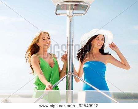 summer holidays and vacation concept - girls on boat or yacht