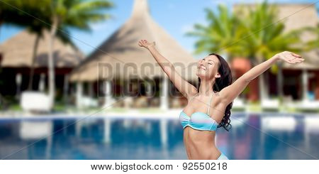 people, summer vacation, travel, tourism and freedom concept - happy woman in bikini swimsuit with raised hands looking up over swimming pool with bungalow and palm trees at hotel resort background