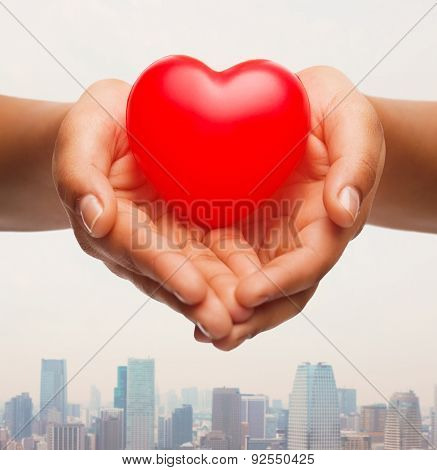 health, medicine, love, valentines day and charity concept - close up of african american female hands holding small red heart over city skyscrapers background