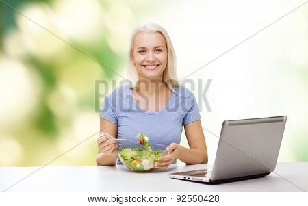 healthy eating, dieting and people concept - smiling young woman with laptop computer eating vegetable salad over green natural background