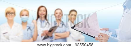 healthcare, cardiology, people and medicine concept - close up of female holding clipboard with cardiogram over medical team