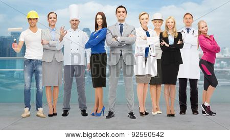 people, profession, qualification, employment and success concept - happy businessman with group of professional workers over city background