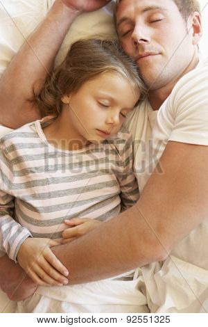 Father And Daughter Sleeping In Bed