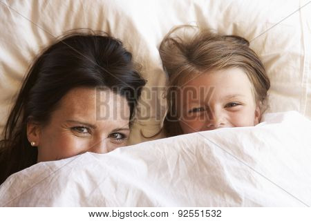 Mother And Daughter Hiding Under Bedclothes