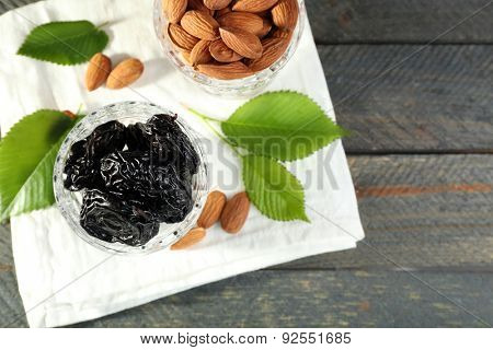 Prunes and almonds in glasses with leaves on wooden table, top view