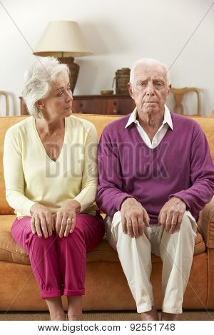 Serious Looking Senior Couple Sitting On Sofa At Home