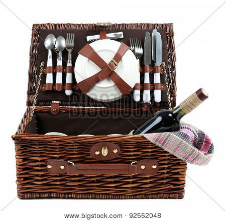 Wicker picnic basket with food, tableware and tablecloth isolated on white