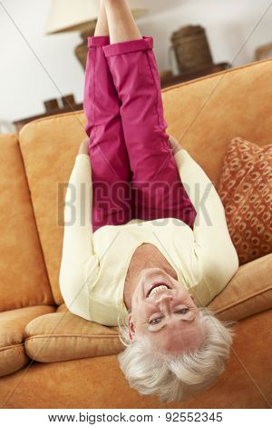 Senior Woman Lying Upside Down On Sofa At Home