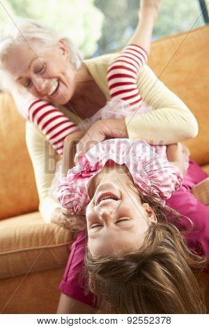 Grandmother And Granddaughter Having Fun On Sofa
