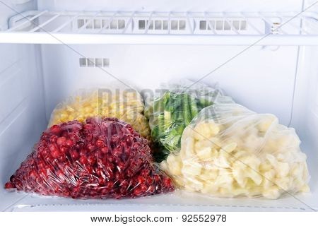 Frozen berries and vegetables in bags in freezer close up