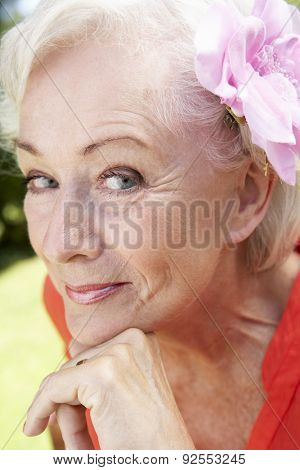 Head And Shoulders Portrait Of Smiling Senior Woman With Flower In Hair