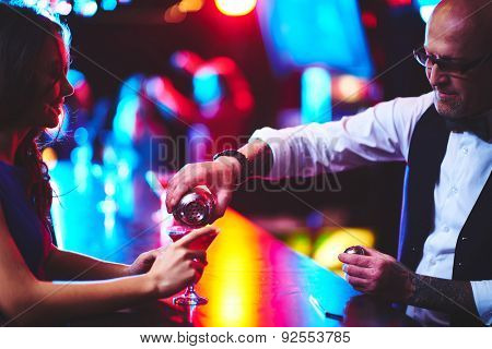 Barman in eyeglasses pouring cocktail to young woman