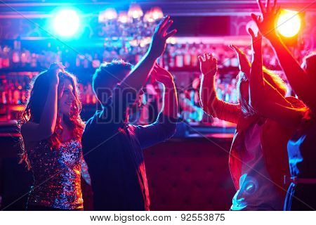 Energetic friends dancing in night club