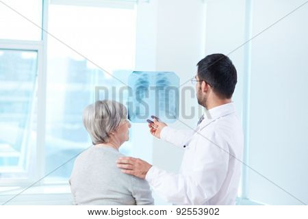 Male doctor showing x-ray to his patient in hospital