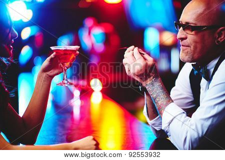 Barman in eyeglasses and young woman with glass of martini communicating at party
