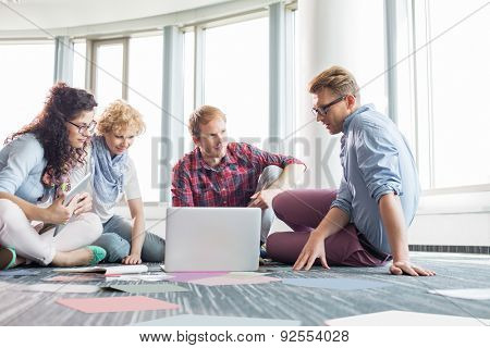 Businesspeople using laptop while sitting on floor at creative office