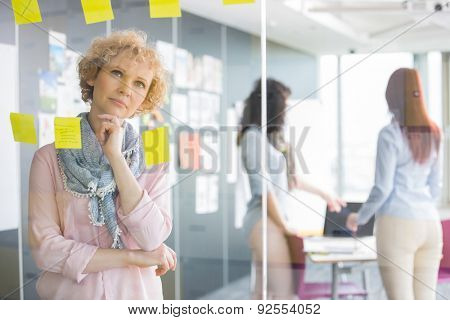 Thoughtful businesswoman reading sticky notes on glass with colleagues in background