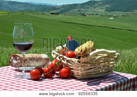 Red wine, bread, sausage and tomatoes on the checkered cloth against Tuscan landscape. Italy