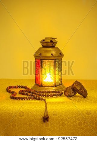 Ramadan festive background. Traditional ramadan lamp with date fruit and islamic prayer beads. Bright golden yellow color scheme.