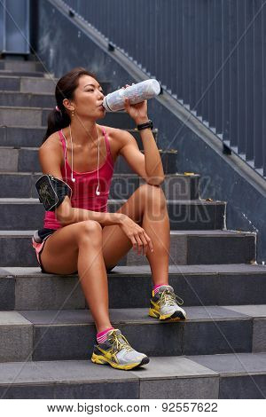 asian chinese sporty woman sitting on steps outdoors quenching her thirst with water bottle after morning workout