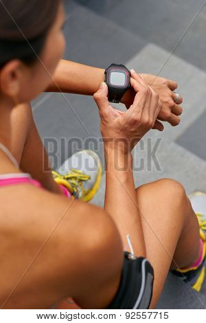 woman sitting outdoors checking workout time on wearable technology watch after run