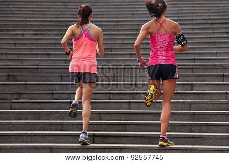 active sporty women working out running up stairs outdoors for morning workout