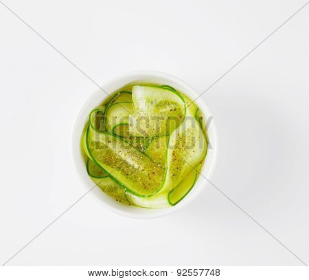 overhead view of sliced cucumbers and sprinkled with spice