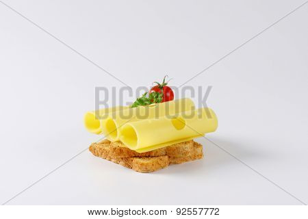 two slices of toast bread with emmental cheese and cherry tomato