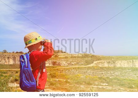 little boy with binoculars hiking in mountains