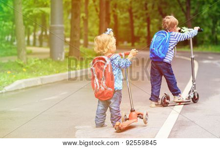little boy and toddler girl riding scooters in the city