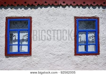 Two windows on the white wall