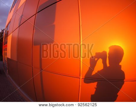 The Silhouette Of A Man On A Red-orange Wall