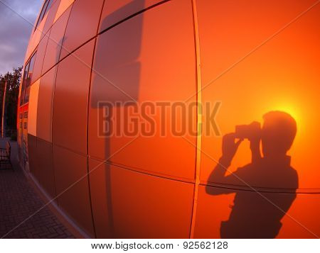 The Shadow Of A Man On A Red-orange Wall