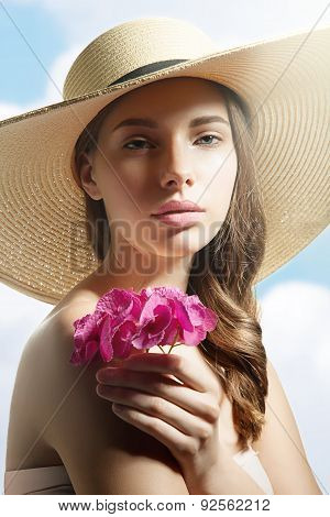 Close-up Portrait Pretty Woman In A Summer Hat With A Flower In Hand Against The Sky