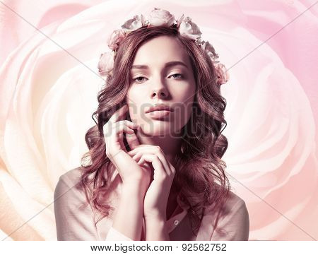 Woman with flowers in hair on background of roses